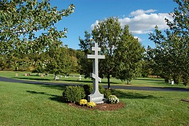 A ten-foot-high granite cross greets visitors at the entrance to the cemetery.